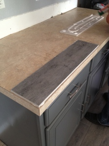 Next, it was time to cover those nasty countertops. And we used the same flooring tile for that!